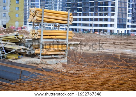 A lot of building materials with metal spare parts, sticks, beams, pipes at an open-air construction site warehouse.