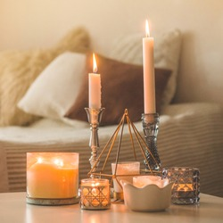 A lot of candles with candlesticks on the home background. Home and home decor. Candles flame. HOME concept