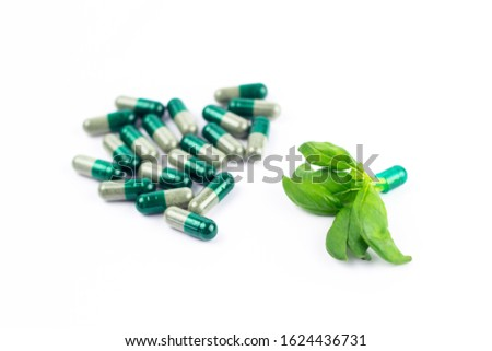 A lot of capsules next to capsule of a dietary Supplement in an open form with herb inside isolated on a white background. Natural ingredients. Healthy natural medicines. Organic vitamin. Close-up