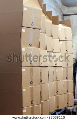 A lot of cardboard boxes arranged up in a stack at an industrial distribution storage room
