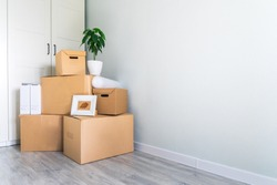 A lot of cardboard boxes with things to move. Check-in to a new apartment or office. Wall and closet in a new empty apartment. Copy space.