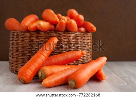 A lot of carrots in a wicker basket. Carrots in a wicker box and next to the box. Orange carrots washed. Carrots for diet and healthy eating. Vintage vegetables on a wooden background.