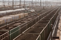 A lot of cars are on the railroad tracks. Freight trains. Freight shipping. Coal, wood planks, gravel, crushed stone. Wagons. Railway carriage.
