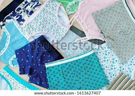 A lot of children's underwear. Underwear for children in the form of shirts and pants. Clothing for girls and boys. Background from underwear of different types. Cotton underwear. Stock fotó ©