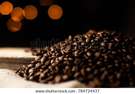 a lot of coffee beans for background, wallpaper, printing image, decorate interior or exterior. aroma drink. fragrance seed. spa therapy. Blur background of yellow lights in the dark #784724437
