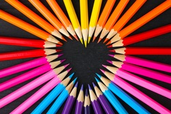a lot of colored pencils closeup on wooden background laid out in the shape of a heart