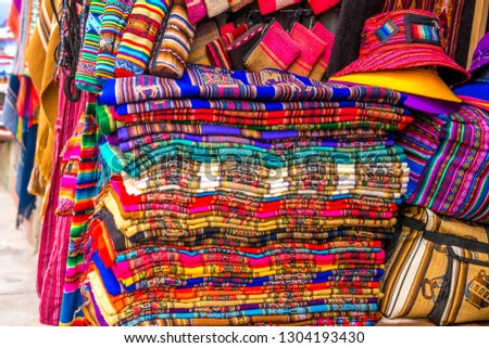 A lot of different colorful fabric coverlets with patterns on the souvenir store in Bolivia