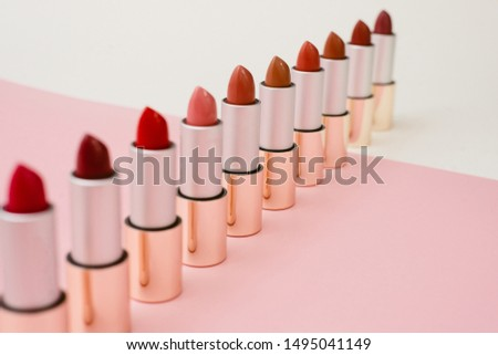 a lot of different lipsticks stand on a beige and pink background. Pattern and concept of beauty, cosmetics, women's accessories. Shades of lipstick tubes.