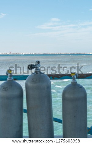 A lot of diving cylinders. oxygen cylinders outdoor. Oxygen cylinders for swimming in the background of the sea. vertical photo #1275603958