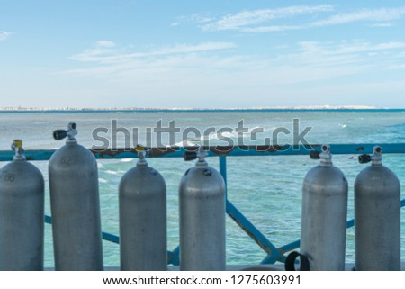 A lot of diving cylinders. oxygen cylinders outdoor. Oxygen cylinders for swimming in the background of the sea. #1275603991