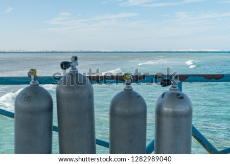 A lot of diving cylinders. oxygen cylinders outdoor. Oxygen cylinders for swimming in the background of the sea. #1282989040