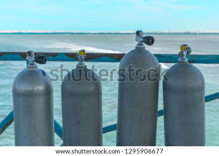 A lot of diving cylinders. oxygen cylinders outdoor. Oxygen cylinders for swimming in the background of the sea. #1295906677