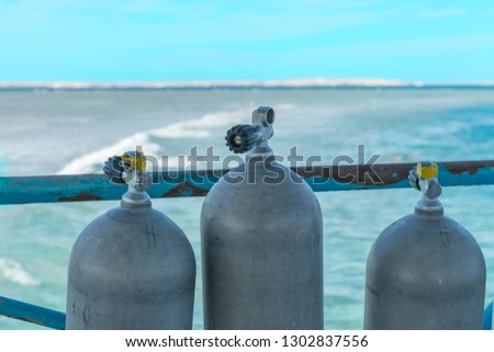 A lot of diving cylinders. oxygen cylinders outdoor. Oxygen cylinders for swimming in the background of the sea. #1302837556