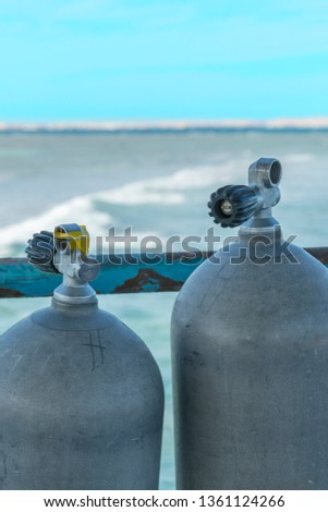A lot of diving cylinders. oxygen cylinders outdoor. Oxygen cylinders for swimming in the background of the sea. vertical photo #1361124266
