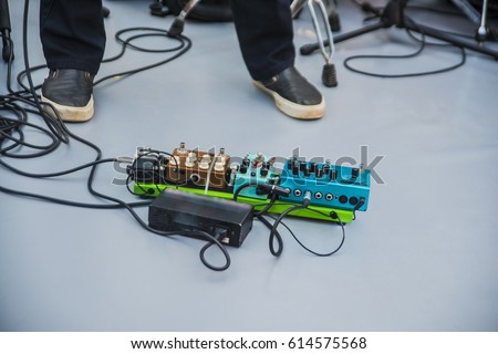 a lot of equipment in a private musical studio with dark wooden floor. guitar audio processing effects on a studio floor. Electric guitar and stomp box type effectors and cables on studio floor.