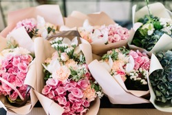 A lot of flower bouquets at the florist shop on the table made of hydrangea, roses, peonies, statice, eustoma in pink and sea green colors