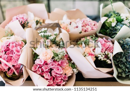 A lot of flower bouquets at the florist shop on the table made of hydrangea, roses, peonies, mattiola, eustoma in pink and sea green colors #1135134251