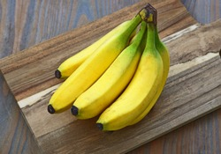 A lot of Fresh Cavendish Banana on wooden background. Health and benefits of Banana