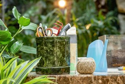A lot of garden accessories on the table in greenhouse