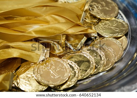 A lot of gold medals with yellow ribbons on a silver tray, awards of champions, sport achievements, first place, prize for the winner #640652134