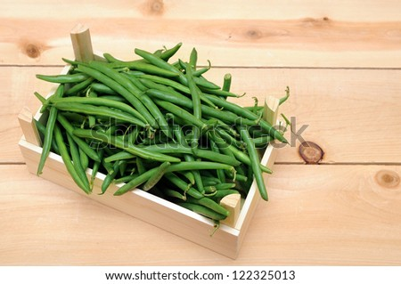 a lot of green beans in wooden case