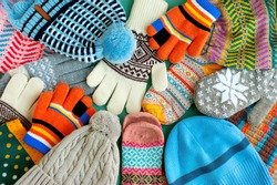 A lot of hats, gloves, mittens. Warm clothes in the form of knitted hats, mittens, gloves, scarves for the cold seasons. Multi-colored clothes for autumn and winter.