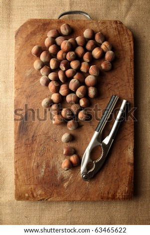 a lot of hazelnut on a wooden table with nutcracker
