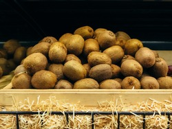 A lot of kiwi in a wooden box on a shelf in a supermarket.