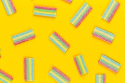 A lot of multi-colored jelly sweet candies on a yellow background. space for text