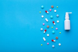 A lot of multi-colored pills on blue background with free space for text, as a concept of medical treatment with a prescription. Painkillers and antibiotics variation, allergy on medicine.
