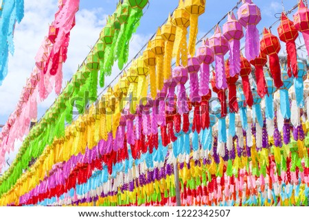 A lot of multicolored mulberry paper lanterns hanging on line rope and blue sky background , decorations for celebration loy krathong festival in lamphun of Thailand #1222342507