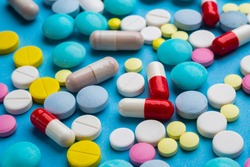 A lot of multicolored pills and capsules on a blue background as a concept of addiction from medicine. Vitamins to keep immunity on a high level.
