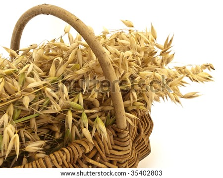 A lot of oats in wicker basket on a white background