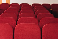 a lot of old chairs without people in the hall for performances and movies. in the frame fragments of the back of the red seats.