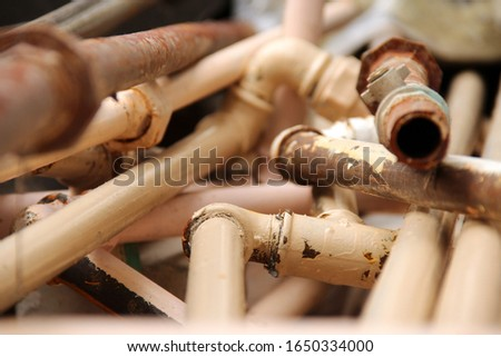 A lot of old rusty pipes and painted pipes.