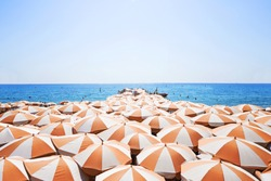 A lot of orange white sun umbrellas on a beach, with a view of a horizon line over the sea, sky, a symbol for holiday vacation