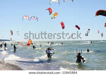 A lot of people kiteboarding in sunny day