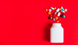 A lot of pills spilling out of a bottle on the red background. Medicine pills, tablets and capsules with copy space for text