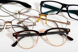 a lot of reading glasses on the white table