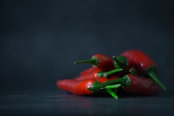 a lot of red chili pepper on dark ground