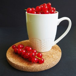 a lot of red currant berries in a white mug on a brown stand on a dark background side view . summer seasonal red berries