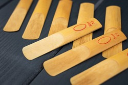 A lot of reeds for a mouthpiece of a wooden instrument on gray wooden background