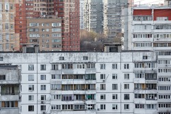 A lot of residential buildings in a cheap quarter. Residential anthill. Old dilapidated housing in a city. Dirty facade of the building. Urban landscape of multi-storey housing in a urban district.