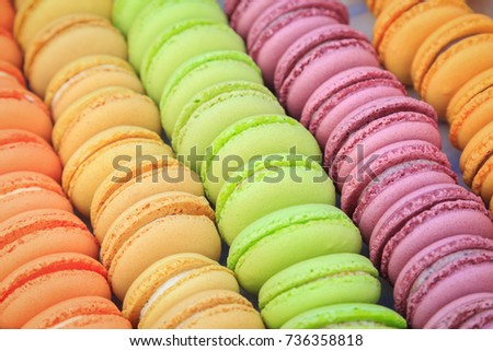A lot of round biscuits with peach flavors, hazelnuts flavors, pistachios flavors, raspberries flavors are stacked in a row in the box #736358818