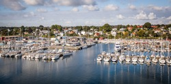 A lot of sailing, motor yachts and boats moored in the marina against the background of the city and the sea. Panoramic image