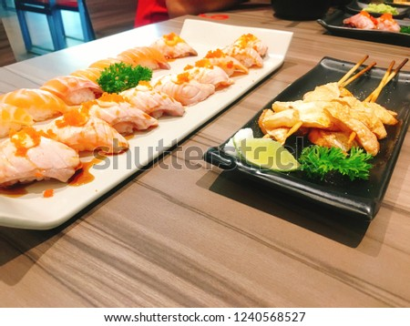A lot of Sushi and Grilled fish fillet in plate place on wood table. Concept for present Japanese food's menu in restaurant. Blur picture.