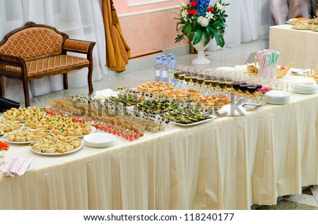 a lot of sushi rolls and drinks on buffet table, catering