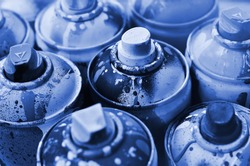 A lot of used spray cans of paint close-up. Dirty and smeared cans for drawing graffiti. The concept of a sweeping and careless drawing of paint. phantom classic blue color