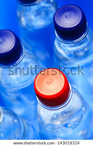 A lot of water bottles with blue caps with a single red-cap bottle among them.