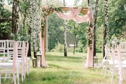 A lot of white chairs and the arch for a wedding